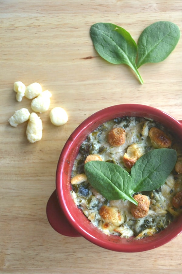 Chicken Florentine Casserole in a red bowl on a wood table with some moon cheese and green leaves on the table
