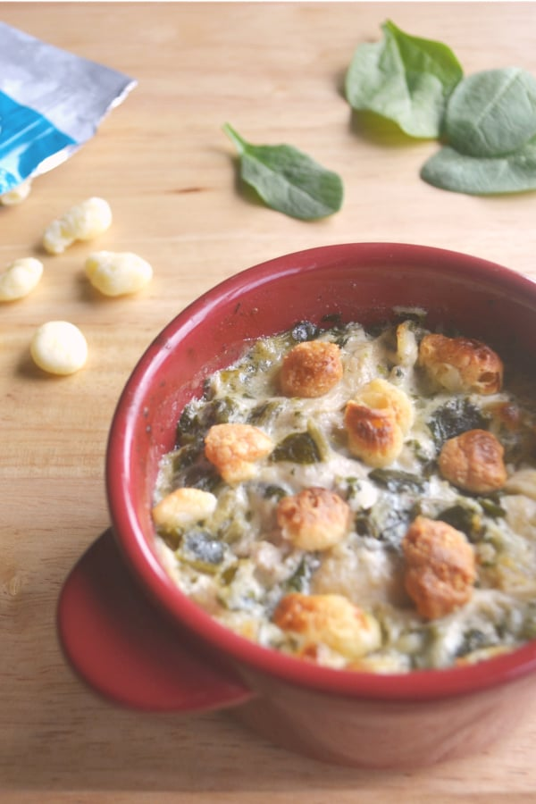 Chicken Florentine Casserole in a red bowl on a wood table next to a bag of moon cheese with some cheese and green leaves on the table