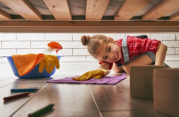 a girl looking under the bed while wearing gloves and holding a rag