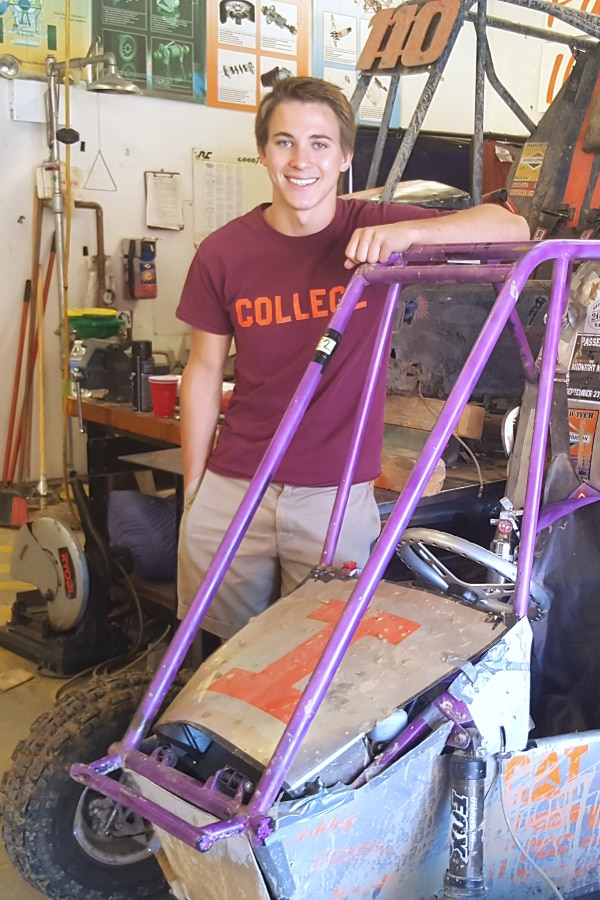 a young man standing leaning on a car he's building in a shop