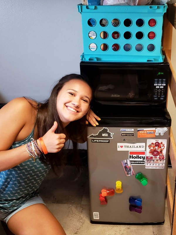 a young woman sitting down giving the thumbs up next to a small freezer, microwave and plastic tub