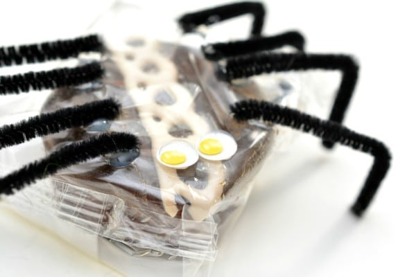 a packaged cupcake decorated with black pipe cleaners as legs, to look like a spider on a white background
