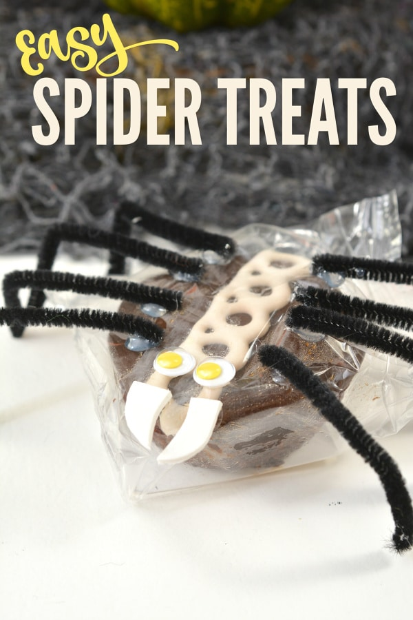 a packaged cupcake decorated with google eyes, white foam as teeth, and black pipe cleaners as legs, to look like a spider on a white background with a black netting in the background with title text reading Easy Spider Treats