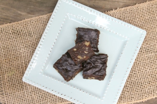 overhead view of brownies on a white plate on a piece of burlap