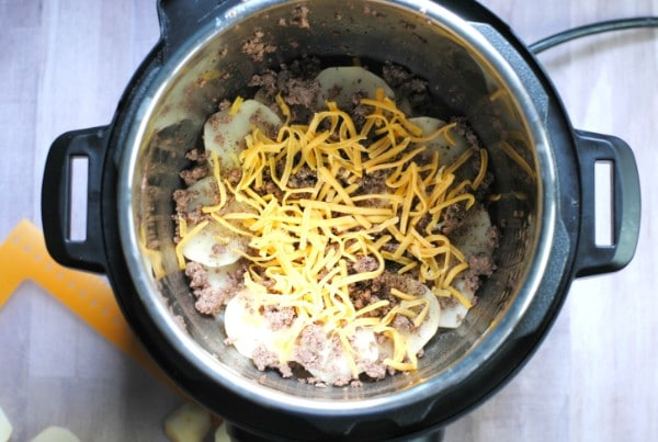 overhead view of potatoes, ground beef, shredded cheese and seasonings in an instant pot on a brown table