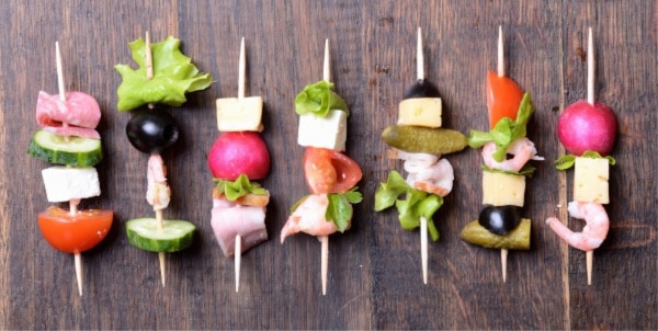 seven skewers with a variety of meat, vegetables, and cheese on them on a wood table
