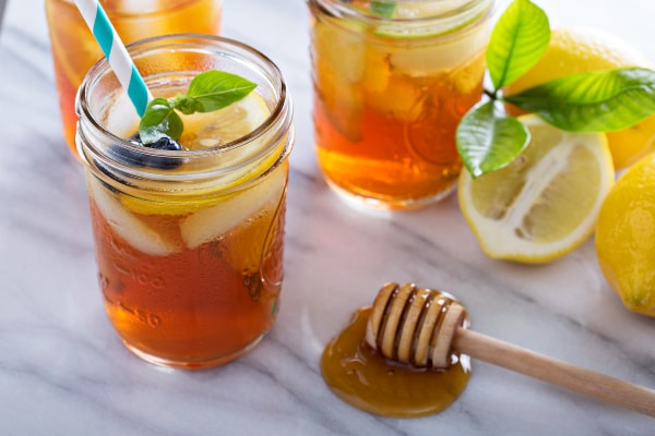 three mason jars filled with iced tea, one with a straw in it, next to a wooden stick in honey and some lemons on a counter