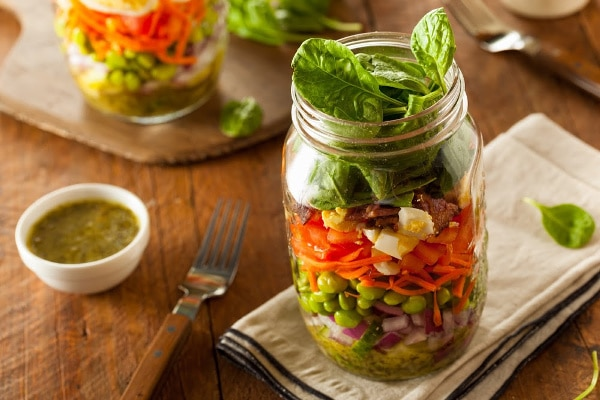 a mason jar layered with salad ingredients on a tan napkin on a brown table next to a fork and a small white bowl of dressing with another mason jar and fork in the background