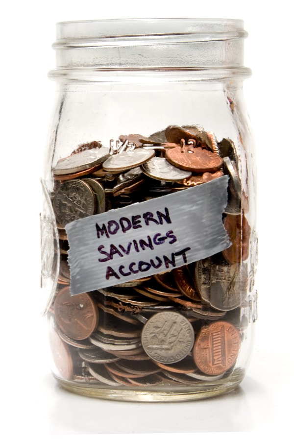 a mason jar filled with coins labeled with the text modern savings account