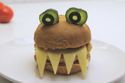 a burger decorated with cheese as teeth, pickles and olives as eyes to look like a monster on a white plate on a white background