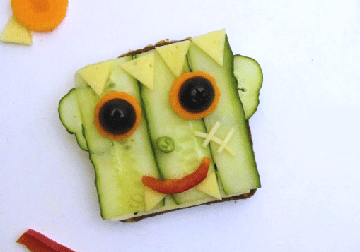 a sandwich decorated with cucumbers, olives, carrots, peppers and cheese to look like a monster on a white background