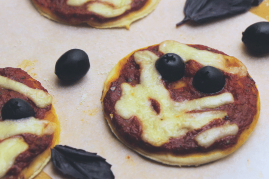 mini pizzas decorated with cheese and olives to look like mummies on a white background