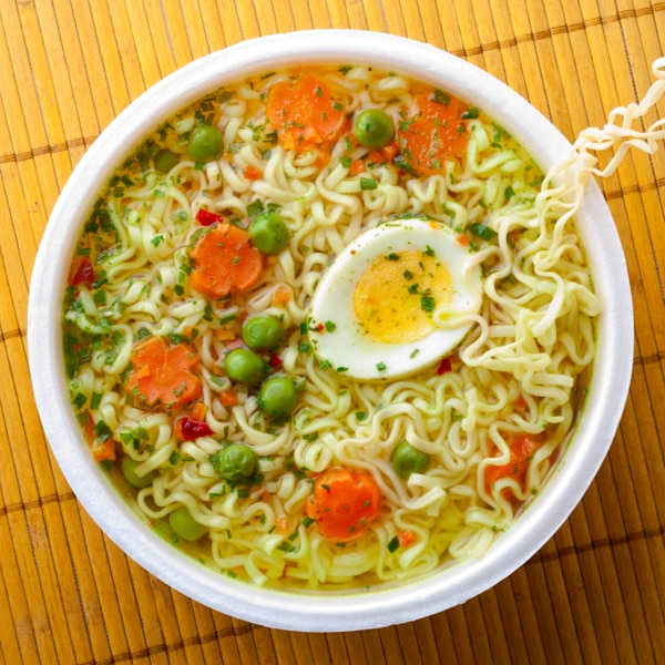 ramen noodle soup topped with carrots, peas and a slice of egg on a bamboo mat