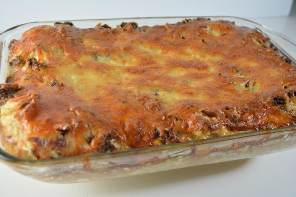 baked sausage croissant breakfast casserole in a glass baking dish on a white table