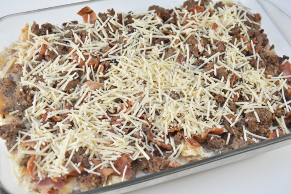 croissants, sausage, bacon and sauce topped with shredded cheese in a glass baking dish on a white table