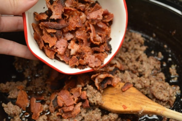 a hand pouring crumbled bacon from a small bowl into the skillet of sausage with a wooden spoon in it