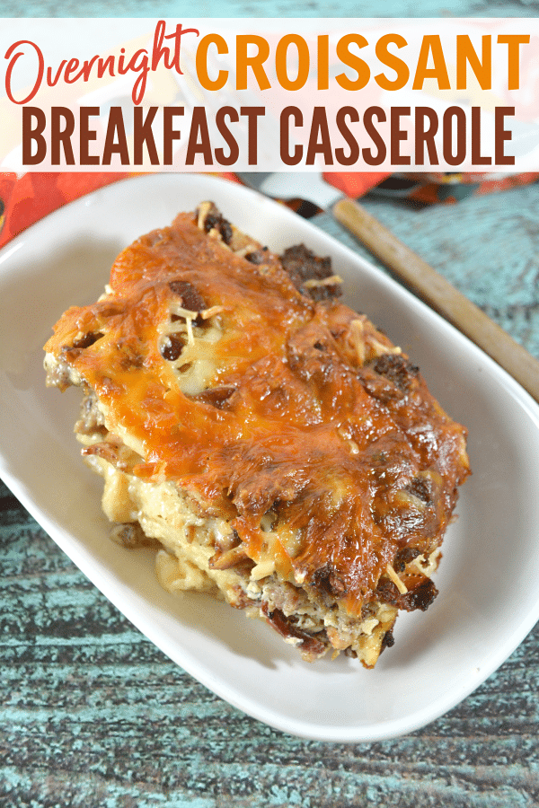 a breakfast casserole in a white dish on a wood table with a fork and flower cloth in the background with title text reading Overnight Croissant Breakfast Casserole