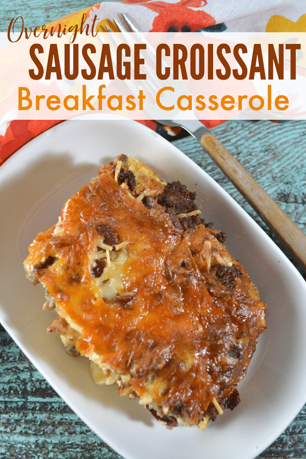 a breakfast casserole in a white dish on a wood table with a fork and flower cloth in the background with title text reading Overnight Sausage Croissant Breakfast Casserole