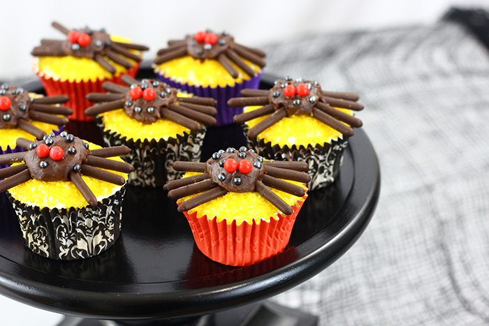 cupcakes decorated with things on top to look like spiders on a black cake stand.