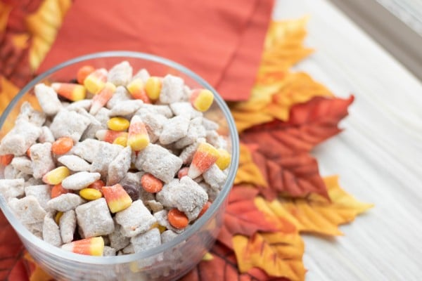 a glass bowl of chex mix with candy corn and m&Ms on fake leaves with a napkin in the background