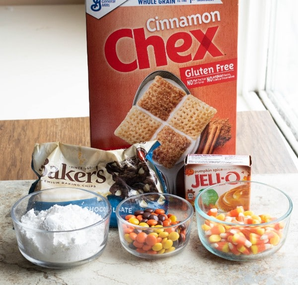 a box of cinnamon chex, a bag of white chocolate chips, a box of jell-o pumpkin spice, glass bowls of confectioners sugar, m&ms and candy corn on a counter with a table and window in the background