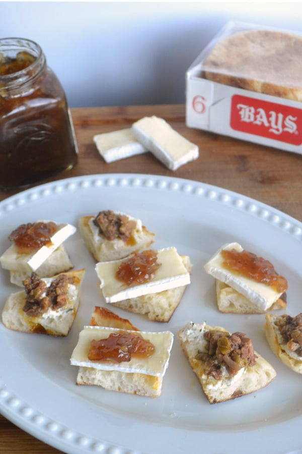 a plate of cut up English muffins topped with cheese and jam or olive tapenade next to a jar of jam, slices of cheese and box of Bays english muffins on a wood table