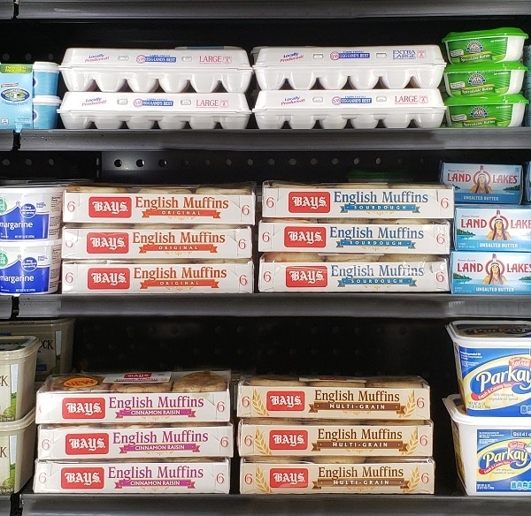 a picture of shelves in a grocery store with eggs, butter, and Bays english mffins