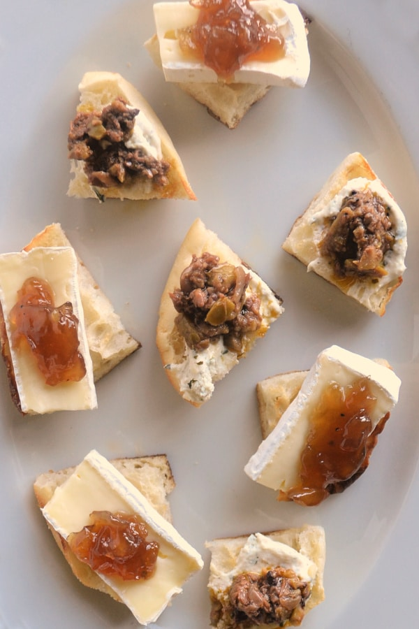 a close up view of a plate of cut up English muffins topped with cheese and jam or olive tapenade