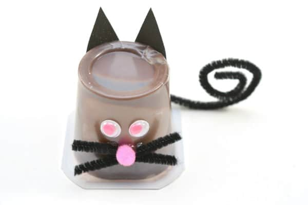 An upside down chocolate pudding cup decorated with paper, googly eyes, pink pom pom ball, black pipe cleaner to look like a black cat