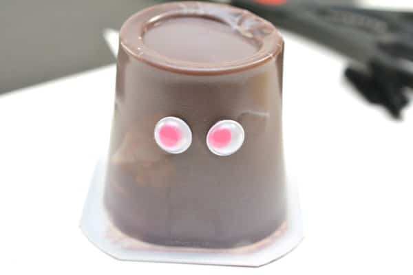 An upside down chocolate pudding cup decorated with googly eyes on a white table