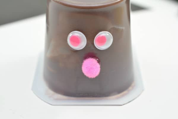 An upside down chocolate pudding cup decorated with googly eyes and a pink pom pom ball on a white table