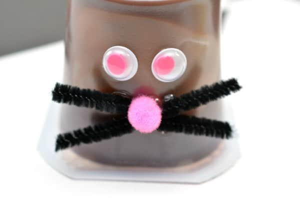 An upside down chocolate pudding cup decorated with googly eyes, pink pom pom ball, black pipe cleaner on a white table