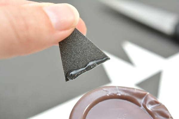 a hand holding black card stock in the shape of a triangle with glue on it next to a chocolate pudding cup