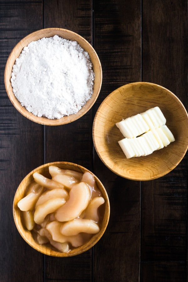 caramel apple pie filling, golden butter cake mix and butter in three wood bowls on a dark wood table