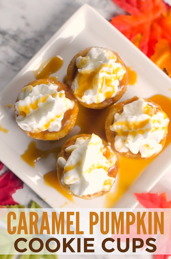 baked cookie cups filled with canned pumpkin, topped with whipped cream and caramel sauce on a white plate on a white counter with fake leaves around the plate with title text reading Caramel Cookie Cups