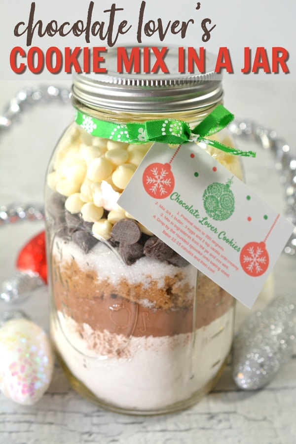 a mason jar filled with layered ingredients to make cookies with a card tied on it with a green ribbon with Christmas light decorations in the background with title text reading Chocolate Lover's Cookie Mix in a Jar