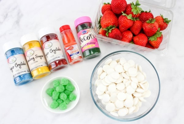containers and bowls of sugar crystals in various colors, green gumdrops, white chocolate melts, and strawberries on a kitchen counter