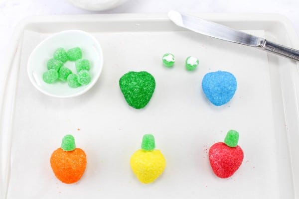 strawberries coated with colored sugar, some with a green gumdrop on top to look like Christmas lights, some waiting for the gumdrop to be placed