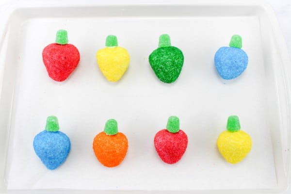 strawberries coated with colored sugar with a green gumdrop on top to look like Christmas lights on parchment paper