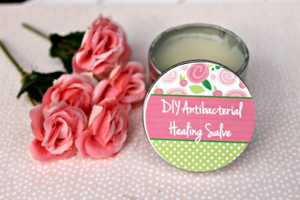 a jar and a lid with DIY Antibacterial Healing Salve in it and written on the lid next to pink roses on a pink and white polka dotted linen