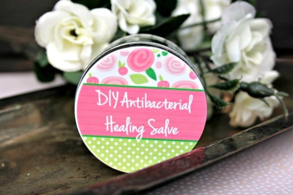 DIY healing salve next to white flowers on a metal tray
