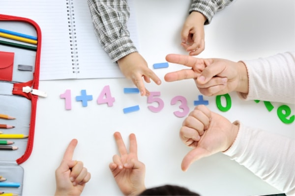 kids using their fingers and foam numbers to make math equations next to a notebook and colored pencils on a table