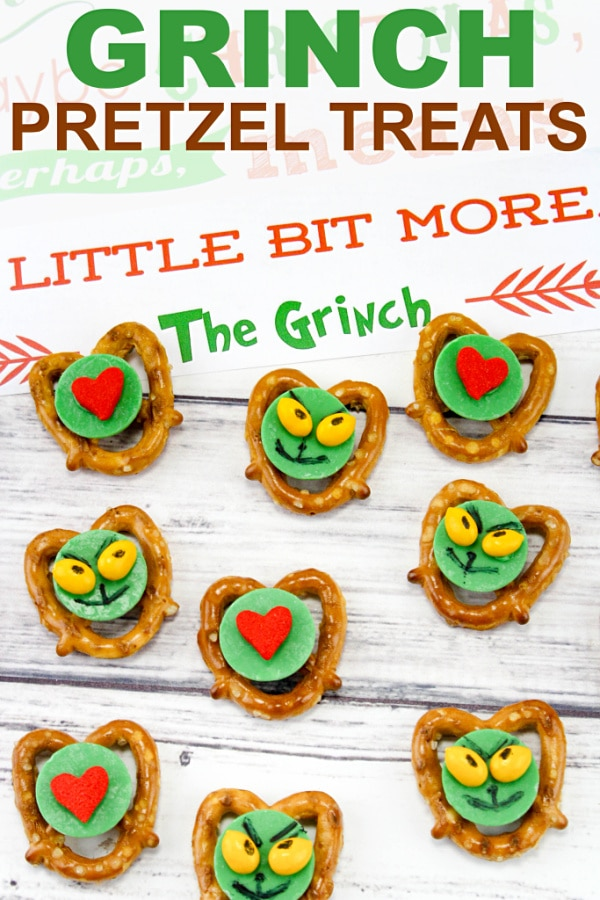 pretzels, green, red and yellow candy decorated to look like the grinch on a table with a phrase from the Grinch book written on a paper in the background with title text reading Grinch Pretzel Treats