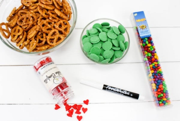 Twist Mini Pretzels, Green Chocolate Candy Melts, Candy Sunflower Seeds, Candy confetti Hearts, Black Food Writer Marker in containers on a white table