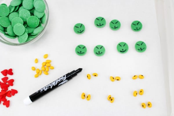 green candy melts with a face drawn on next to yellow candy coated sunflower seeds with eyes drawn on next to a food marker, more sunflower seeds, red heart candy, a bowl of green candy melts all on a white table