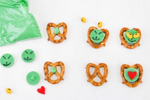 pretzels, green candy melts, candy coated sunflower seeds and a bag of green icing in various stages of being made to look like the Grinch on a white table