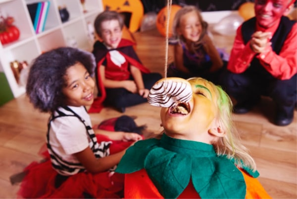 kids in Halloween costumes sitting on the floor watching a kid trying to eat a donut from a string