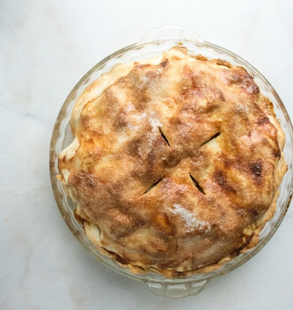 baked apple pie in a glass pie dish on a white counter