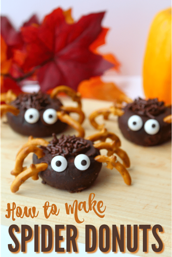 three mini chocolate donuts decorated with chocolate frosting and sprinkles, pretzels and candy eyes to look like spiders on a brown table with fake leaves and a pumpkin in the background with title text reading How to Make Spider Donuts