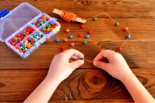 a child lacing beads on a string on a brown table